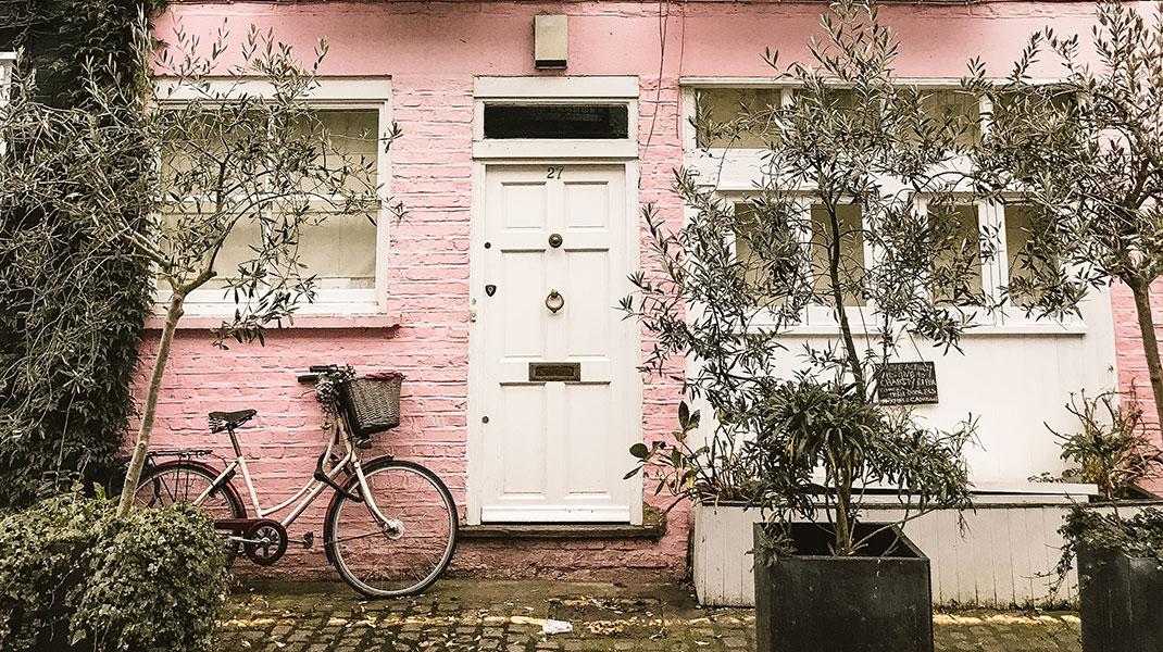 Rosafarbene Hauswand mit weißer Tür und einem Fahrrad.