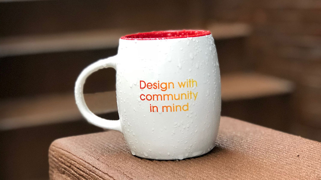 picture shows a mug that says: Design with community in mind
