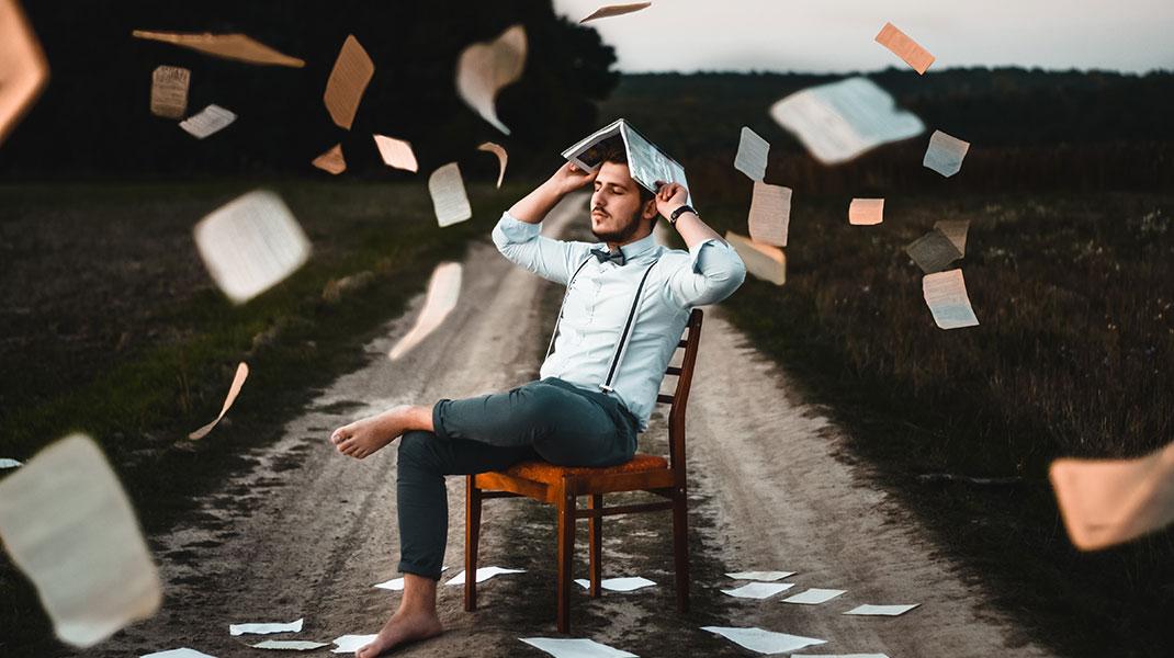 Mann sitzt auf einem Stuhl im Freien und die Blätter eines Buches fliegen in der Luft.